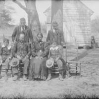 Six People near Wood Frame Building 1900.jpg